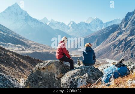 Pareja linda descansando en la ruta de senderismo Everest base Camp cerca de Dughla 4620m. Hombre sonriendo a woman.Backpackers izquierda mochilas y bastones de senderismo y..