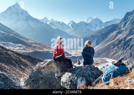 Pareja linda descansando en la ruta de senderismo Everest base Camp cerca de Dughla 4620m. Hombre y mujer disfrutando de un descanso.dejaron mochilas y bastones de trekking y