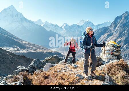 Pareja siguiendo la ruta de senderismo Everest base Camp cerca de Dughla 4620m. Backpackers llevar mochilas y utilizando bastones de senderismo y disfrutar de la vista del valle