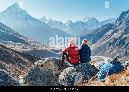 Pareja descansando en la ruta de senderismo Everest base Camp cerca de Dughla 4620m. Backpackers izquierda mochilas y bastones de senderismo y disfrutar de la vista del valle con