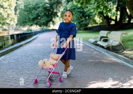 Niña africana de 5 años de edad, camina y juega con su cochecito de juguete en el parque. Lindo bebé de piel oscura con un cochecito y un oso de peluche