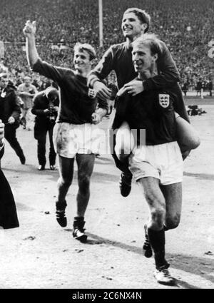 30 de julio de 1966 Wembley Stadium, Inglaterra. 1966 final de la Copa Mundial, Alemania contra Inglaterra.Jack Charlton lleva Alan Ball como Roger Hunt (l) sigue la parte trasera después de vencer a Alemania 4-2 después de que se juega tiempo extra. Foto de stock