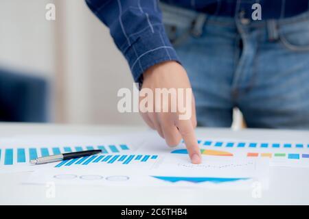 Mano de un joven hombre de negocios señalando datos de documento gráfico y papel gráfico, marketing e inversión, informe de las estadísticas de beneficios para los financieros, económicos