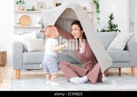 Mamá feliz jugando con el hijo niño en casa, peeking desde debajo de la manta Foto de stock