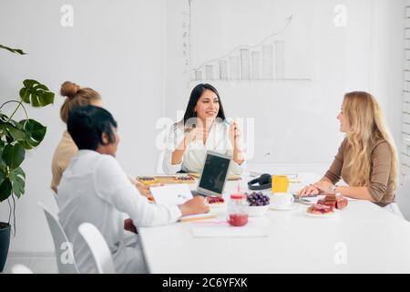 Jóvenes mujeres de negocios interactuando durante el descanso del café en la conferencia de negocios en la oficina blanca, frutas y una taza de té en la mesa Foto de stock