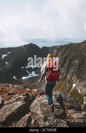Mujer camino corriendo en las montañas con mochila roja viaje estilo de vida senderismo solo activo vacaciones de verano al aire libre aventura viaje en Noruega