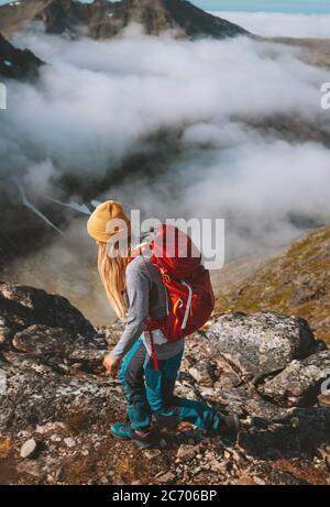 Mujer senderismo en las montañas con mochila roja viaje pista de carrera actividad vacaciones de verano estilo de vida saludable aventura al aire libre solo trekking en Noruega