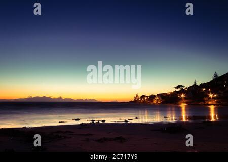 Vista del amanecer sobre False Bay desde Fish Hoek Beach con montañas en el fondo, Ciudad del Cabo, Sudáfrica Foto de stock