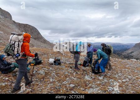 Backpackers poner en equipo de lluvia como el tiempo tormentoso se acerca en un sillín por debajo de Europa Peak. Wind River Range, Wyoming