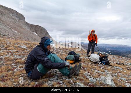 Un mochilero macho se pone en el equipo de lluvia como el tiempo tormentoso se acerca en un sillín por debajo de Europa Peak. Wind River Range, Wyoming