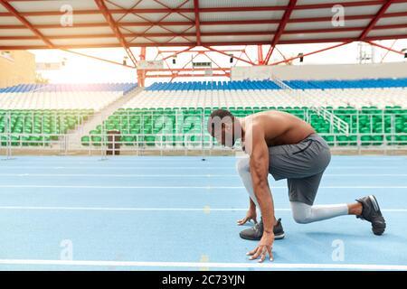 el talentoso corredor africano está listo para sprint, hombre parado en la posición de inicio bajo, foto de vista lateral completa. espacio de copia