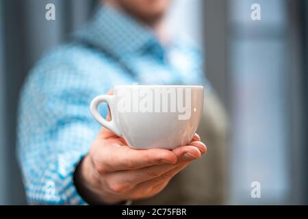 Primer plano de Man Barista estirando la mano con la taza de café. Desayuno perfecto. Concepto de estancia en casa. Preparando café por Amateur en la cocina casera