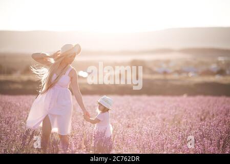 Joven mujer sonriente sosteniendo a una niña de 1-2 años caminando en la pradera de lavanda al aire libre sobre la luz del sol al fondo. Temporada de verano. Enfoque selectivo.