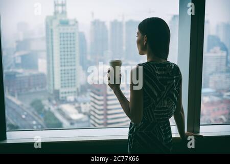 Mujer de negocios bebiendo café en el trabajo contemplativo mirando por la ventana del edificio rascacielos de gran altura durante el descanso del té de la mañana. Estrés, mental Foto de stock