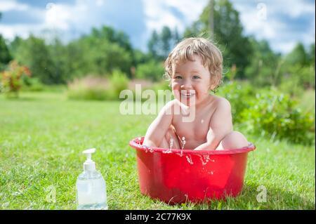 El bebé se lava en el baño sobre la hierba verde. El bebé se divierte, salpican agua y se ríe. Niño feliz bañándose al aire libre en césped verde adentro