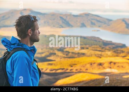Hiker man en Nueva Zelanda caminata de senderismo pisotear en el sendero al aire libre paisaje de montaña. Joven tranvía caucásico caminando con mochila al atardecer en la naturaleza