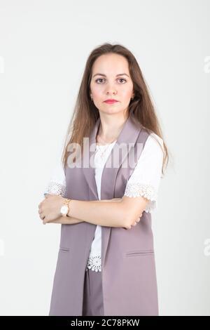 hermosa mujer joven en el negocio ropa estricta posan contra una pared blanca