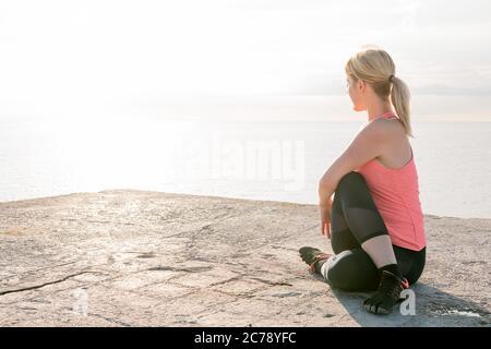 hermosa mujer rubia practica yoga estirándose al amanecer sentado frente al mar, concepto de salud mental y relajación, espacio de copia para texto