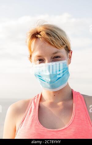 retrato vertical de una bella rubia con una máscara protectora con el cielo en el fondo, concepto de prevención y atención de salud