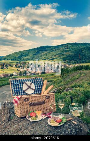 Cesta de picnic francesa retro vintage con pan de queso y vino Gewürztraminer en los viñedos sobre el pueblo medieval de Riquewihr Alsacia Francia