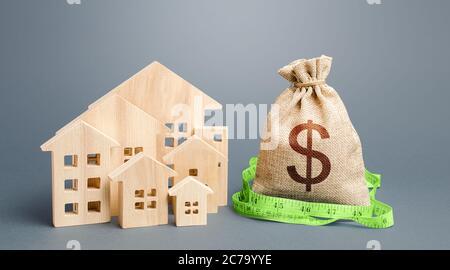 Casas residenciales y una bolsa de dinero en dólares. Valoración inmobiliaria. Compra y venta, precio justo. Cálculo de gastos, construcción y r Foto de stock