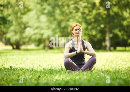 Serena mujer madura de pelirroja sentada sobre hierba y sosteniendo las manos en Namaste mientras meditaba en el parque vacío