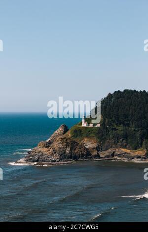 Disparo vertical de un faro en un acantilado rodeado por los árboles junto al mar bajo un cielo azul Foto de stock
