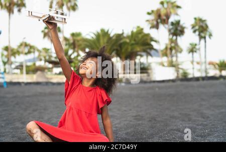 Niño afro jugando con el avión de juguete de madera en la playa - niño pequeño divertirse durante las vacaciones de verano - niños y viajes concepto de vacaciones