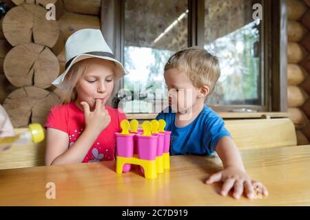 Dos adorables rubia caucásica hermano pequeño sentado en el patio de la casa de la mesa y divertirse degustación mamá helado de fruta casero. Joven hermana feliz y..