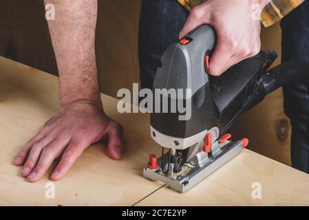 Hombre con jig eléctrico vio cortar madera
