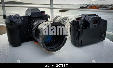 Dos cámaras negras en un barco con muelles en el fondo Foto de stock