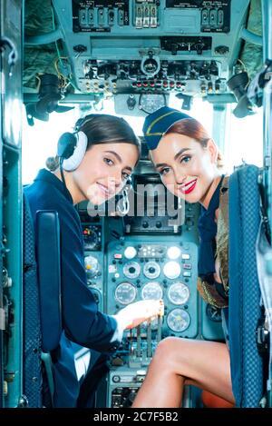 Dos hermosas mujeres piloto con uniforme. Mirando la cámara a través de la cabina. Pilotos en cabina. Chicas mirando cámara. Feliz y exitoso