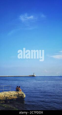 Tiro vertical de un faro en la orilla del océano bajo el cielo despejado Foto de stock