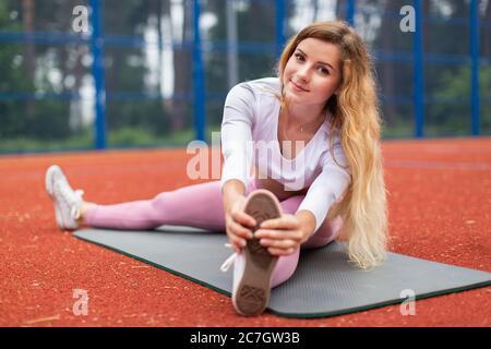 Retrato de una mujer rubia sonriente atractiva estirándose antes de la aptitud y el yoga. Mujer en rosa sportswear haciendo ejercicio de estiramiento, sentada en la estera