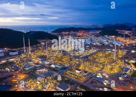 Vista aérea de la fábrica de productos químicos de la planta de refinería de petróleo y de la planta de energía eléctrica con muchos tanques de almacenamiento y tuberías al atardecer.