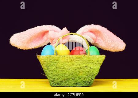 Orejas de conejito de Pascua y cesta llena de huevos de pascua pintados sobre mesa de madera amarilla aislada sobre fondo negro. Pascua y concepto de regalo