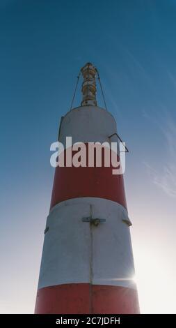 Tiro vertical de bajo ángulo de un faro rojo y blanco bajo el hermoso cielo brillante Foto de stock