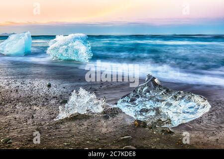 Increíbles piezas del iceberg brillan en la famosa playa Diamond Beach en la laguna Jokulsarlon durante la puesta de sol. Ubicación : laguna Jokulsarlon, Playa de diamantes, V Foto de stock