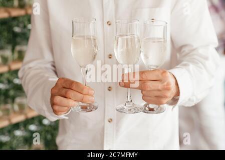 Hombre sin rostro vestido de camisa blanca sosteniendo tres copas de champagne en sus manos