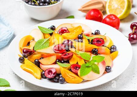 Ensalada de frutas con bayas en un plato blanco, fondo blanco. Concepto de comida vegetariana saludable.