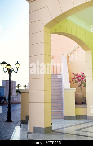 Edificio moderno del hotel con arcos arquitectónicos, escaleras y lámparas de calle cerca de la casa en un día soleado de verano, espacio de copia. Concepto de viaje de verano.