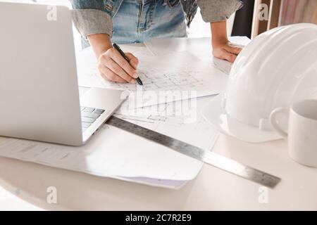 Ingenieros que sostienen un bolígrafo que apunta a un edificio y que utilizan el portátil para planificar el calendario del proyecto. Concepto de ingeniería y construcción.