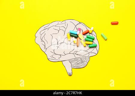 Cerebro humano y pastillas sobre fondo de color. Concepto de demencia