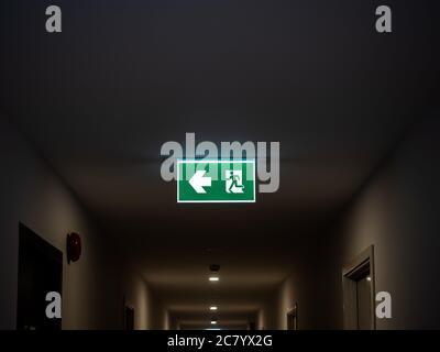 Salida de incendios. Señal de salida de emergencia verde iluminada colgando en el techo en un edificio moderno en la oscuridad del apartamento.