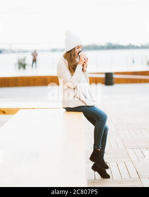 Hermosa niña bebiendo café, té de la taza de plástico en otoño, invierno. Una mujer con el pelo largo sentado en la orilla del mar Báltico en el puerto y.