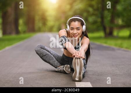 Entrenamiento de fitness al aire libre. Chica asiática sonriente estirándose en el parque y escuchando música