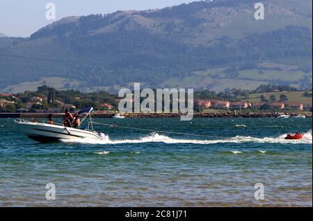 Velero de movimiento rápido remolcando gente en un anillo de goma naranja inflado en la bahía de Santander