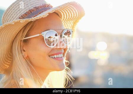 Una chica rubia sonriendo con sombrero encendido - Playa y la luz del sol reflejada en gafas de sol - hermosas mujeres jóvenes en vacaciones - Retrato foto