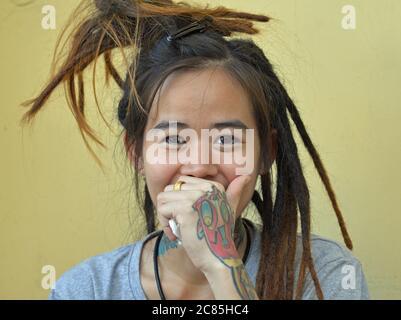 Una joven tailandesa con largos y sólo medio acabados dreadlocas rastafarianas posan para la cámara y cubre su boca con su mano izquierda tatuada.