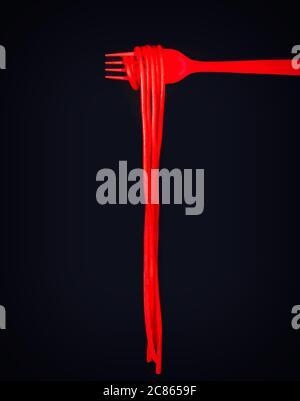 Comida mágica. Espaguetis rojos en una horquilla roja, fondo negro y espacio de copia